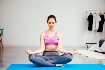 Young Caucasian woman doing yoga meditation in lotus pose position at home