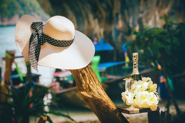 closeup woman white hat with black ribbon on tree trunk near champagne bottle at flowers