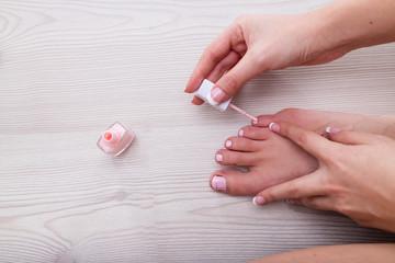 hand of a woman applying pink nail polish