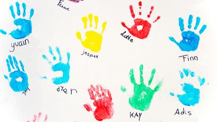 Bunte Handabdrücke von Kinderhänden auf weisser Wand mit Namen