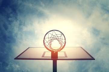 Basketball hoop on basketball court under blue sky with clouds