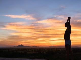 Young woman enjoying outdoors, sky background,sunset