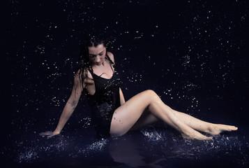 Pretty brunette woman  in black dress  under the water drops in aquastudio sitting in water