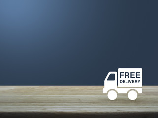 Free delivery truck icon on wooden table over light blue gradien