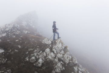 Man climbing to the top of mountan in the foggy and very cold we