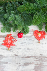christmas fresh evergreen tree twigs with red vintage heart and star decorations on white wood close up