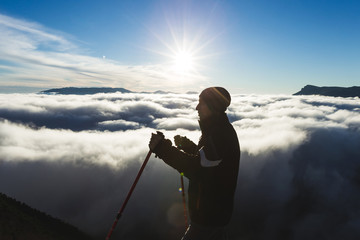 Silhouette of a climber high in the mountains above the clouds a