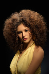 Brunette girl with a curly hairstyle, modern make-up and carnivore look