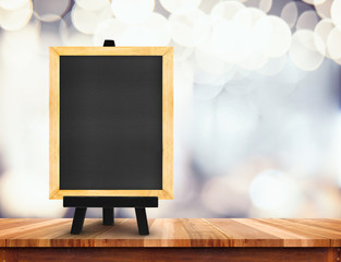 Blackboard with easel on wood table at blurred coffee shop backg