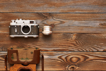 Vintage old camera and lens on wooden background