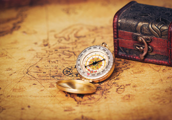 Old vintage compass with treasure Chest on map.