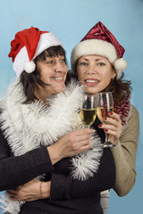 Girl in Santa Claus hats and champagne