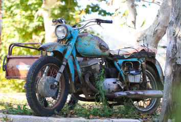Old vintage rusty motorcycles in field close up. Antique.