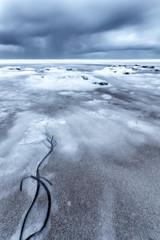 Porthtowan beach in cornwall england UK with the foam on a slow exposure making it look like snow.