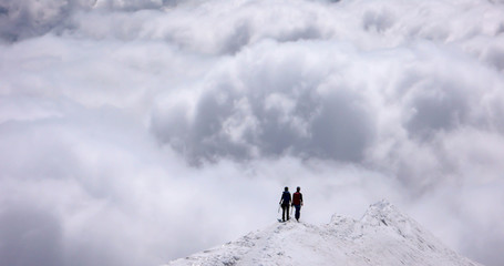 a mountain guide and client on an exposed rise in the Swiss Alps headed into an oncoming storm