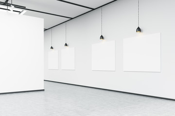 Corner of art gallery with large white wall and pictures