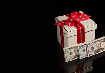 Dólares en billetes y caja con lazo rojo.