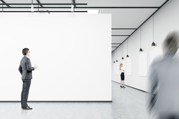 Men and a woman are looking at empty banners in an art gallery
