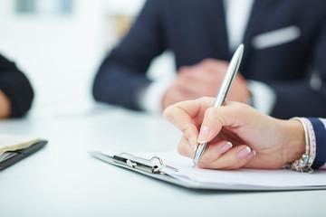 Female hands holding a silver pen closeup.  Business job offer, financial success, certified public accountant concept.