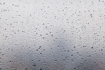 Rain drops on window glasses surface with cloudy background . Na