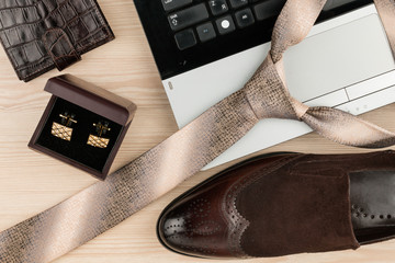 Fashion and business, notebook, shoes, cufflinks, tie on a wooden table as background.