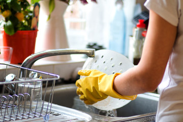 Woman washing dishes in the kitchen. Close up of  woman hand. Housewife clean dishes.