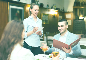 Cheerful waitress taking a table order