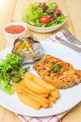Grilled meat steak serve with tomato sauce, Mashed Potatoes, french fries and vegetable salad, isolated on wooden background, Closed up
