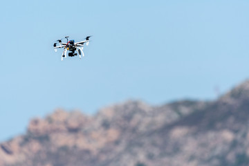 Drone with camera hovering over mountains