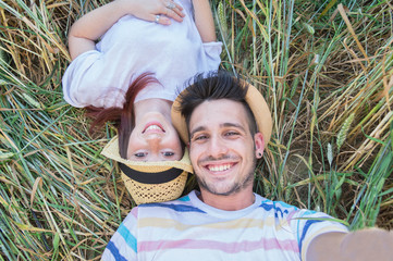 Loving couple taking a selfie lying on the grass at vacation.