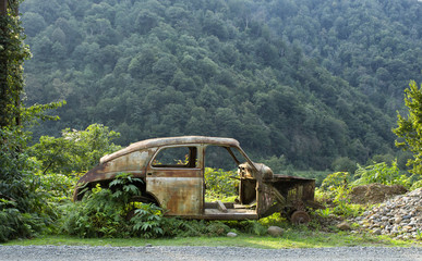 Destroyed rusty car in the mountains of Georgia