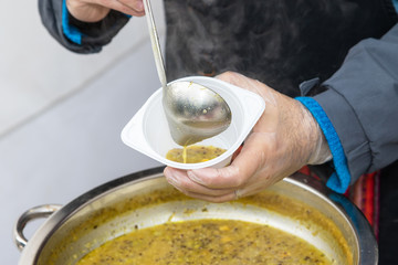 Street food - Stallholder selling corn soup into a plastic bowl. All potential trademarks are removed.