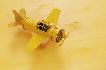 image of retro yellow metal toy airplane over wooden table