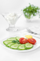 Sliced tomato, cucumber and half of an egg on a plate,white background. High key  selective focus.