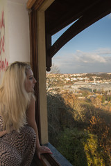 Young woman looking on the city from window