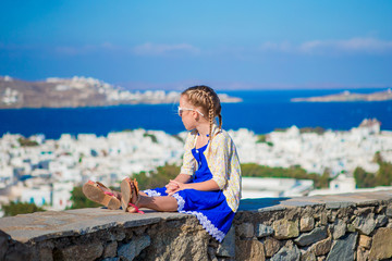 Adorable little girl background Mykonos town in Europe