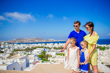 Family vacation in Europe. Parents and kids taking selfie photo background Mykonos town in Greece