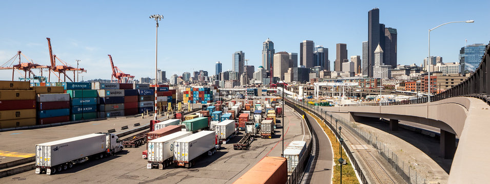Panorama of trucks entering Seattle harbor with skyline in background