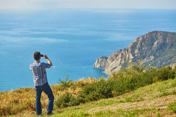 Tourist enjoying the view of Cinque Terre coast, Italy