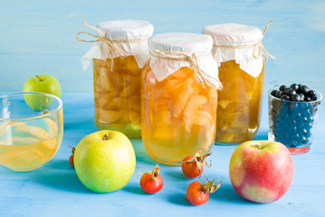 Jam of pears and apples in glass jars on a blue wooden background