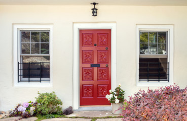 A nice entrance of a ornamented red entry door in luxury house