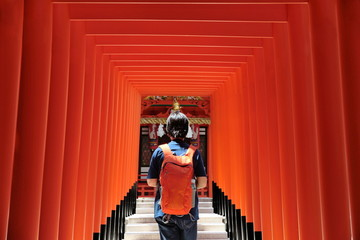 Lady's backpacker in red archs at Ikuta shrine (God of love place) ,Kobe,Japan with selected focus.