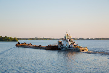 Tug with a barge on Moscow River comes in evening