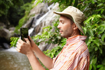 Nature, ecology and science concept. Serious biologist in striped shirt holding touch pad, taking picture or recording video of beautiful wildlife in rainforest while studying its bio-diversity