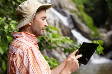 Profile of serious male scientist with stubble taking picture of nature on his black generic digital tablet while working on scientific research in jungle. Botanist using electronic gadget outdoors