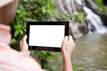 Caucasian scientist or ecologist recording video of wildlife and mountain river in nature reserve, using digital tablet with white blank copy space screen for your advertising content. View from back