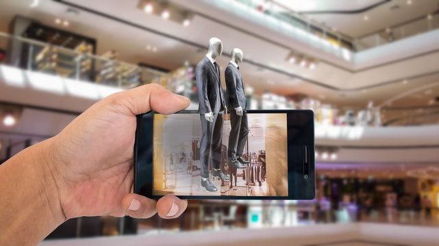 Augmented reality application for retail business concept. Hand holding smart phone with A/R application on screen to finding shop in department stroe.