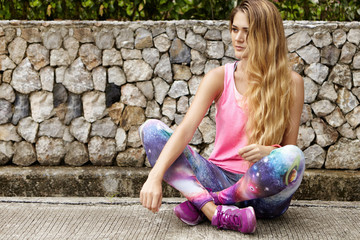 Outdoor portrait of beautiful Caucasian woman jogger with long blonde hair wearing pink sports top and space print leggings sitting and relaxing on stone pavement with legs crossed after long run