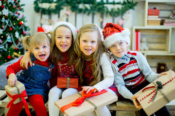 Group of kids in red hat with Christmas gifts