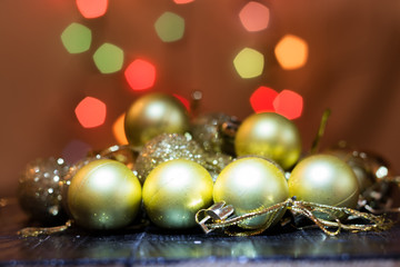 Yellow christmas tree baubles on black wooden table.